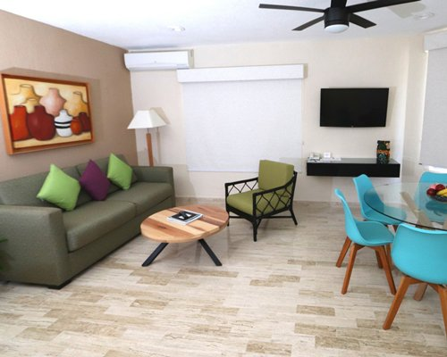 A well furnished living room with dining area television and a view of the water.