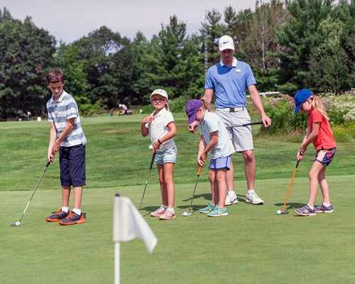 Golf class with 4 young students and instructor practicing their putting.