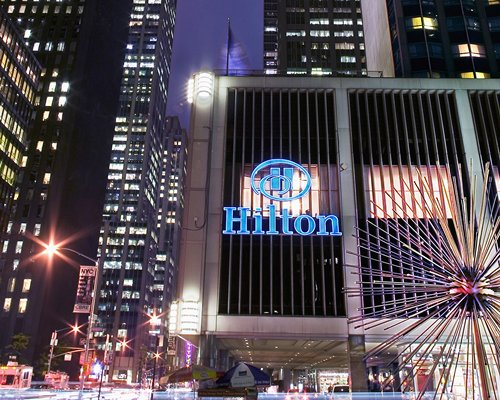 Street view of The Hilton Club of New York at night.