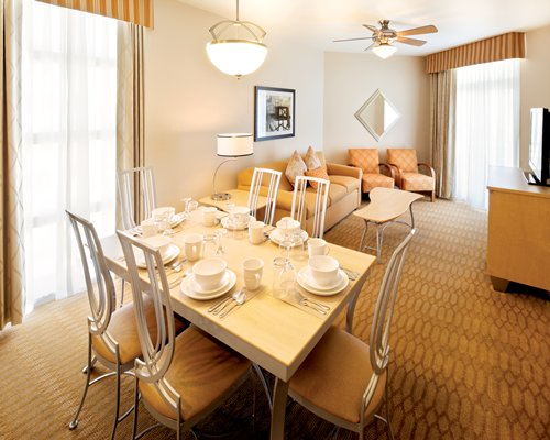 An open plan dining room with a well furnished living room.