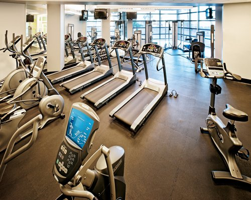 A well equipped gym with an outside view.