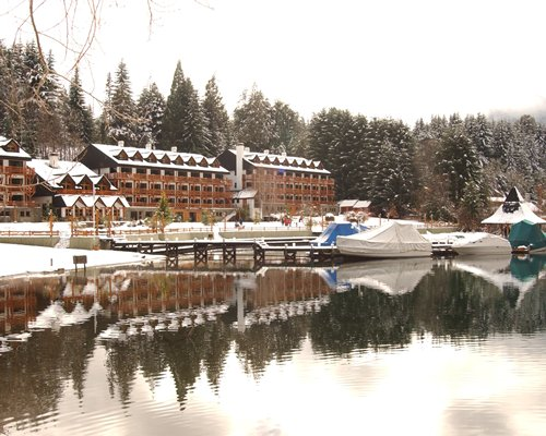 A view of multi story resort condos covered in snow alongside a waterfront.