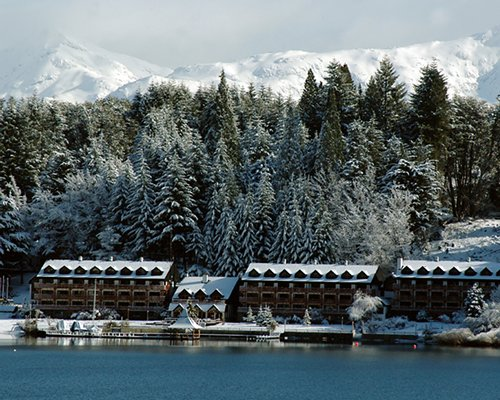A lake view of the resort condos alongside pine trees covered in snow.