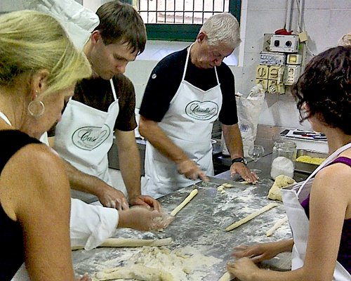 A group of people making pasta.