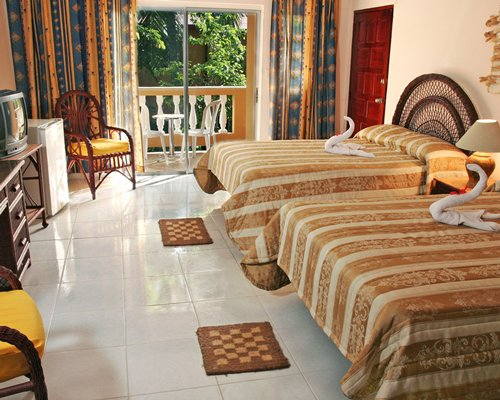 A well furnished bedroom with two beds television balcony and patio chairs.