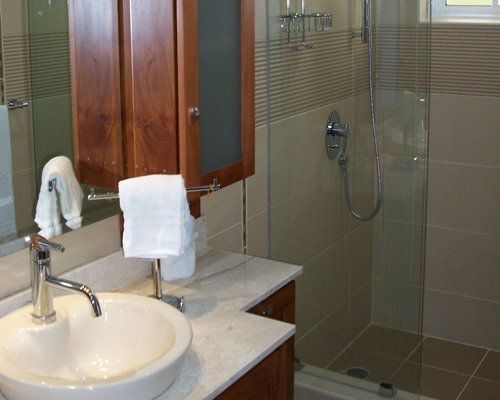 A bathroom with shower and single sink vanity.