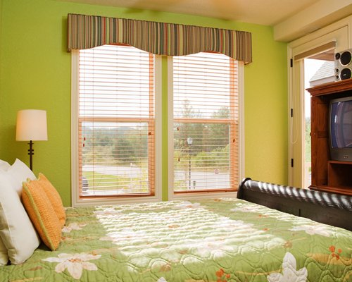 A well furnished bedroom with king bed television and outside view.