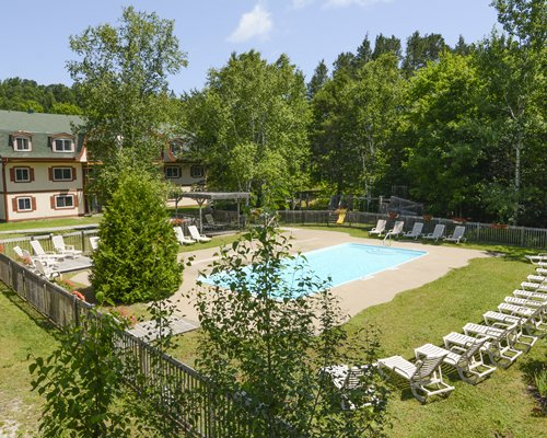 View of Privilege Mont with outdoor swimming pool and chaise lounge chairs surrounded by wooded area.