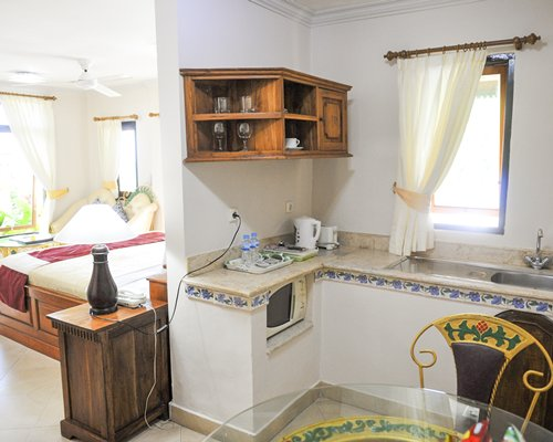 An open plan kitchen with dining area and a queen bed.