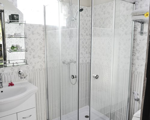 A bathroom with a shower stall and single sink vanity.