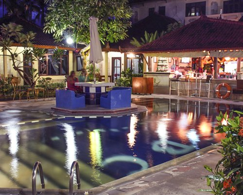 An outdoor swimming pool with patio furniture alongside the resort at night.