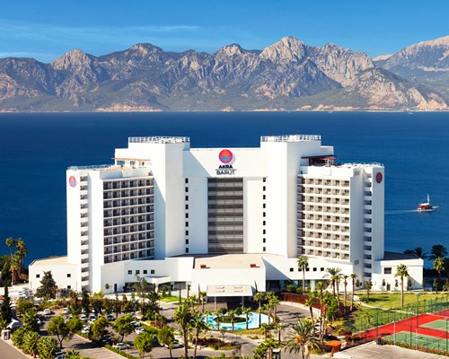 An exterior view of the Akra Hotel alongside the sea and the mountains.