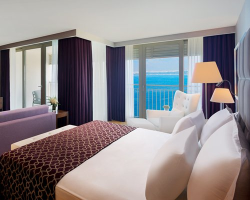 A well furnished bedroom with balcony and sea view.