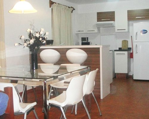 A well equipped kitchen with a glass top dining table.