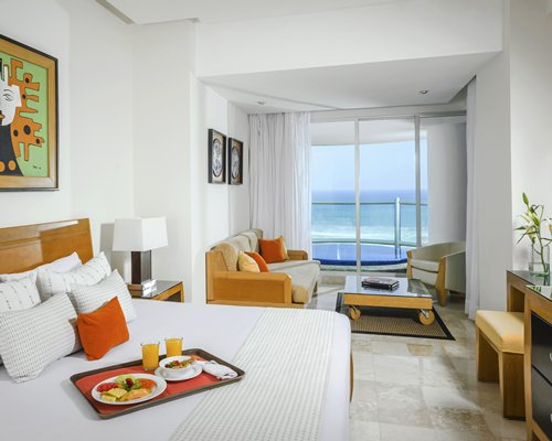 A well furnished bedroom with a king bed and the ocean view.