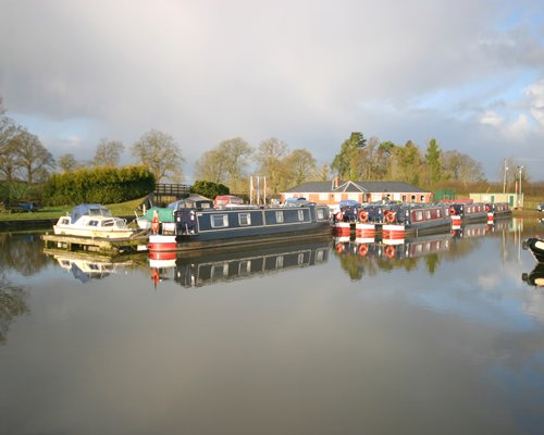 Exterior view of a boat outside of Canalboat Club at Blackwater Meadow.
