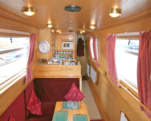 Interior view of a boat with living area and open plan kitchen.