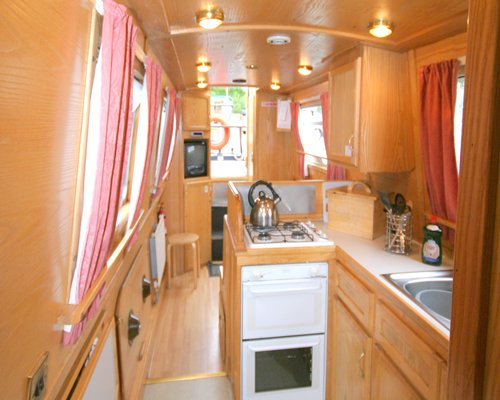 Interior view of the boat with open plan kitchen and television.