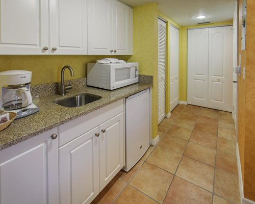 A well equipped kitchen with a breakfast bar alongside a bedroom.