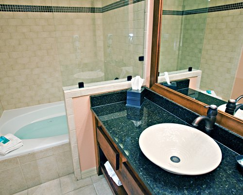 A bathroom with a sink vanity and a shower stand.