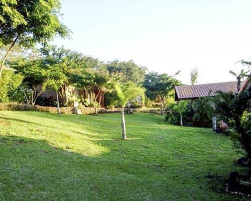 A well maintained lawn alongside resort units and trees.