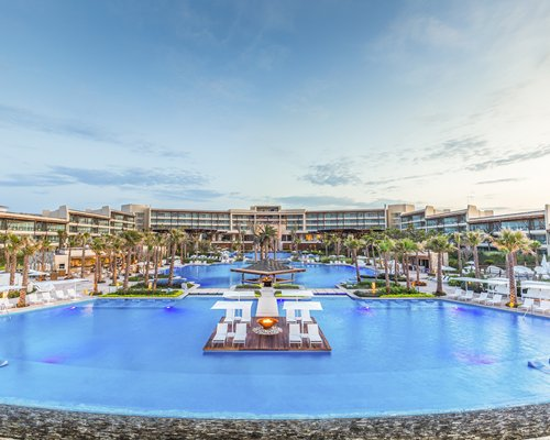 Exterior view of The Grand Mayan at Vidanta Cabos with large outdoor swimming pool and palm trees.