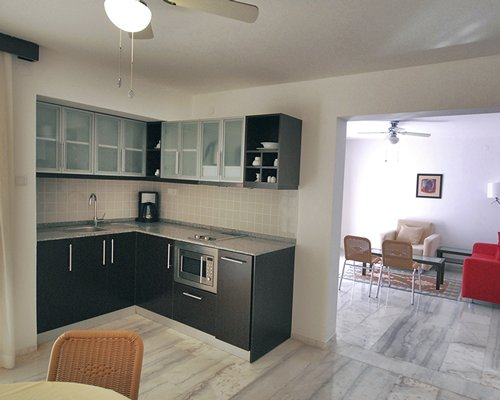 A well equipped kitchen with a microwave oven alongside a living room.