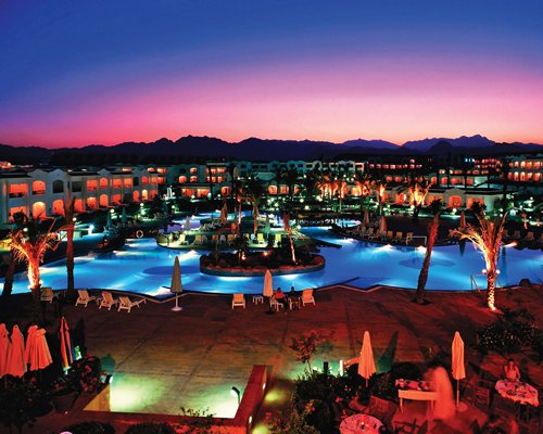 Night view of a large outdoor pool alongside the Sharm Dreams Vacation Club.