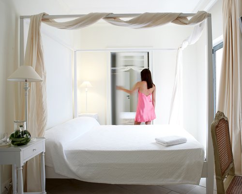 A woman at a well furnished bedroom with outside view.