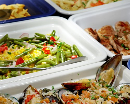 A buffet with vegetables and mussels.