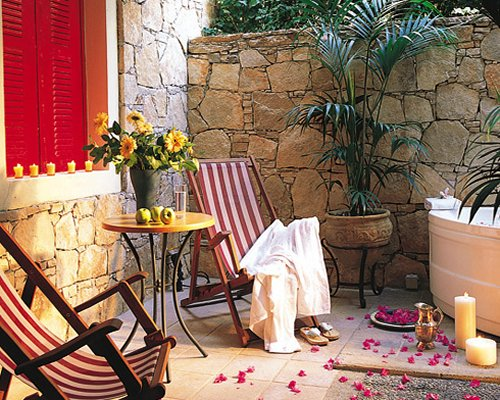 Outdoor hot tub with chaise lounge chairs candles and landscaping.