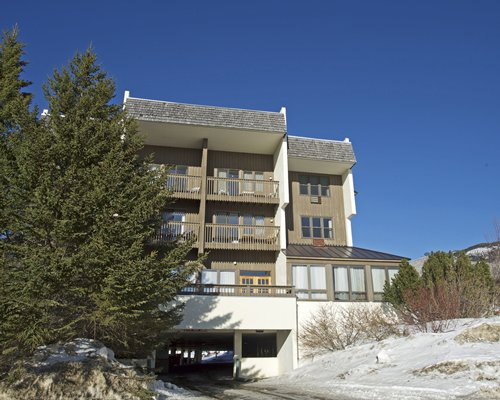 Exterior view of Bolton Valley Resort Lodge with multiple balconies and landscaping.