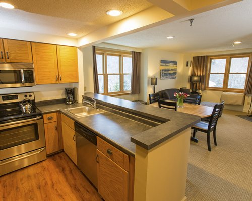 A well equipped kitchen with breakfast bar and living area.