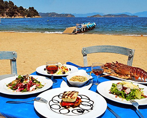 View of various foods placed on an outdoor dining area alongside the sea.