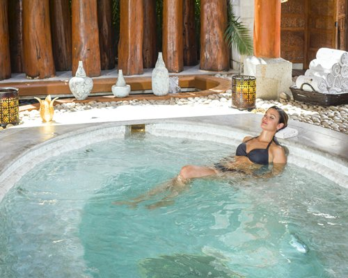 A woman relaxing at an indoor hot tub.