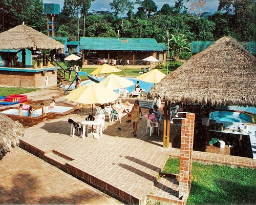 Thatched covered poolside bar next to a large outdoor swimming pool.