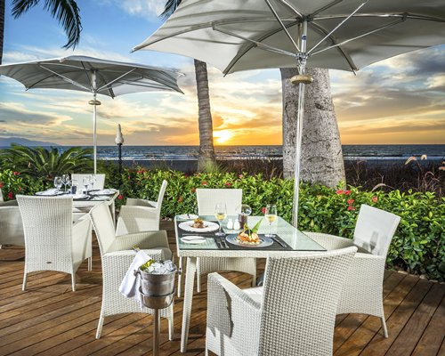 An outdoor fine dining restaurant alongside the ocean.