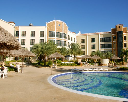 An outdoor swimming pool with patio furniture thatched sunshades and trees alongside multi story resort units.