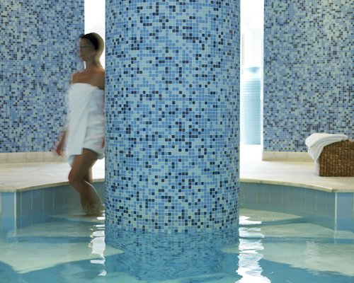 An indoor swimming pool with a fitness area.