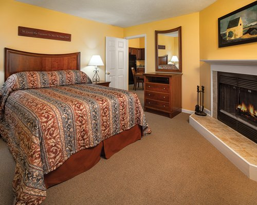 A well furnished bedroom with fireplace.