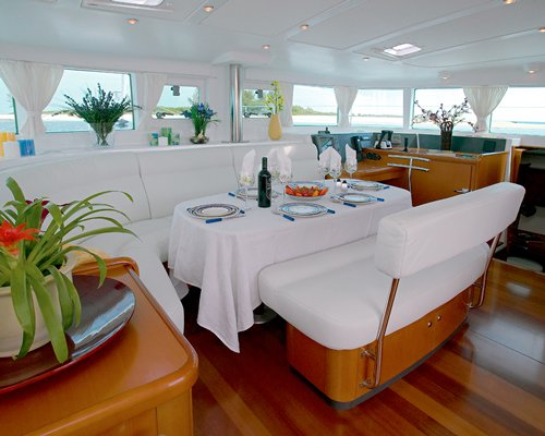 Interiors of a boat with dining area and outside view.