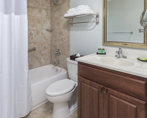 A bathroom with open vanity toilet and bathing area.