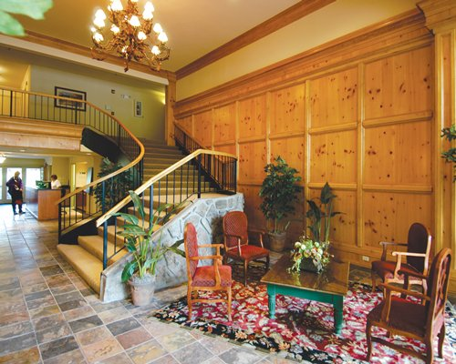 A well furnished reception and lounge area with a stairway.