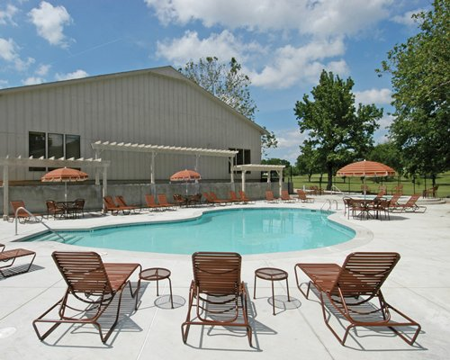 An outdoor swimming pool with chaise lounge chairs sunshades and trees alongside resort units.