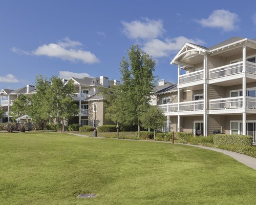 An exterior view of the multi story condos with a paved pathway and landscaping.