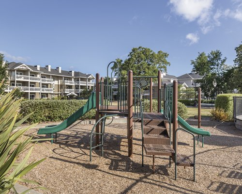 An outdoor play area alongside multi story resort units.