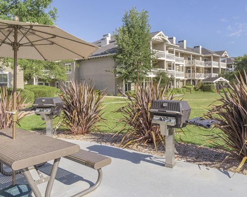 An outdoor dining area with a barbecue grill alongside the multi story resort units.