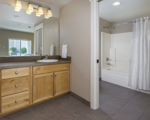 A bathroom with a single sink vanity and bathtub.