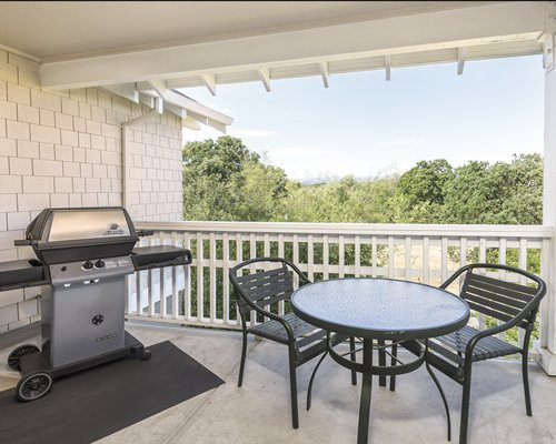 A balcony with a barbecue grill and patio furniture.