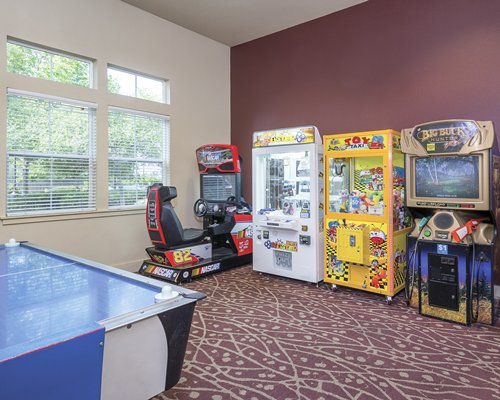 An indoor recreational area with pool table and arcade games.